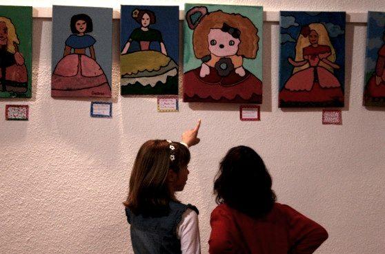 Dos alumnas observan los trabajos expuestos